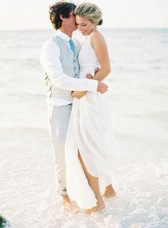 groom in gray vest hugs bride at beach wedding