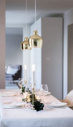 Winter and christmas table decor. Brass, white, green. Artek Golden Bell -lamps, Skultuna Tulip candlesticks, via Coffee Table Diary