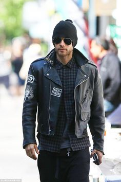 Addicted: Throughout their sunny stroll, Jared - sporting stubble - never let go of his iPhone