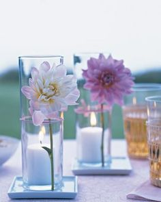 """""""Think Outside the Vase: Go the opposite route of traditional.  This fabulous DIY centerpiece project from marthastewart.com takes things outside the vase.  One simple trimmed floral stem is wrapped on the outside of the cylinder vase, showcasing its sleek beauty, with a colored string or use colored wire.  Slip a votive candle inside the case for a dual arrangement and lighting."""""""