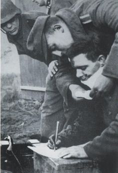 """The picture shows the soldier Alfred Jonstrup from """"Freikorps Danmark"""". He was hit by a Russian grenade and part of his jaw was blown away. Even though he wasn't able to talk he kept on writing down information. A friend is trying to hold a towl under Alfreds jaw so the blood will not hit the paper."""