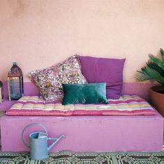 Banquette maçonnée à l\'orientale peinte en rose et agrémentée de coussins et matelas imprimés