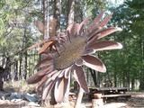 A picture of a metal bee sculpture on one of the giant metal Sunflower sculptures