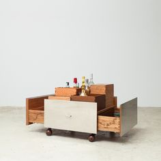 """""""Toto"""" bar cart in freijó wood encased in stainless steel, containing wooden boxes in cedar, freijó, ipê and tauari wood. Leather """"leash"""" allows piece to be moved. Awarded """"Linha de Móveis - Instituto dos Arquitetos do Brasil"""" prize in 2006. Part of the Etel collection."""