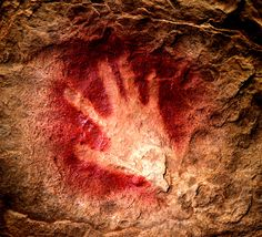 30,000-year-old handprint found in Chauvet Cave in France, made by mixing pigment with saliva inside the mouth and blowing the mixture onto a cave wall, is an emblem of the deep history of human creativity.