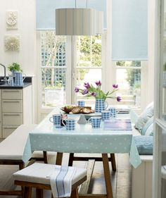 Laura Ashley: cheery and beautifully light and airy breakfast room in pale blue, one of 2014s predicted fashion colours, teamed with putty and ivory together with teak furniture for a thoroughly charming modern scheme. Love the polka dot crockery!