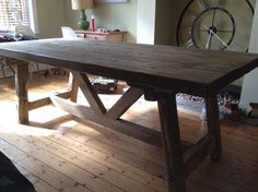 This would be a bad rendition of the style I like - looking mainly at the supprts.  (heavy, thick, interferes with seating)  rustic trestle table - Google Search