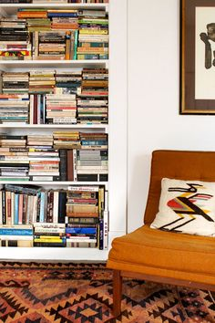 love this packed bookcase (and it's little reading chair!)