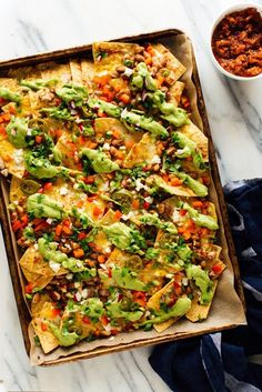 Loaded Veggie Nachos Recipe – Cookie and Kate You're looking at the ultimate vegetarian nacho recipe! No meat, just beans, veggies, lots of cheese and creamy avocado sauce. Veggie Nachos, Vegetarian Nachos, Veggie Recipes, Mexican Food Recipes, Nacho Recipes, Vegetarian Recipes No Cheese, Seafood Recipes, Summer Vegetarian Recipes, Skinny Recipes