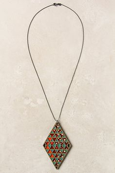 Anthropologie:  This geometric pendant is an illusory outline of shapes in bold shades. Handcrafted of lightweight birch and Dutch superwax cotton.