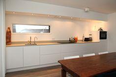 Strakke witte keuken in Oisterwijk, extra diepe 70 cm kasten en een 2 cm composiet blad. Geen hoogglans maar prachtig mat gelakt.