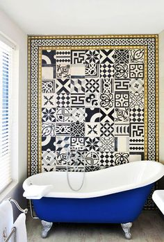 Mix and match patterned black and white tiles and a blue clawfoot tub.