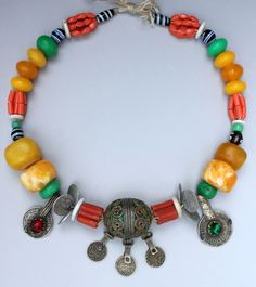A Moroccan necklace from southern Morocco, perhaps Bou Izakarn.  With amber resin, glass jewels, old coins, Venetian beads, glass coral, and a metal tagemout pendant.