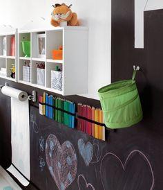 Denne væg kan det hele, det er sejt! Væggen er malet med tavlelak, og den er malet dekorativt som en bygning. Der er monteret en ret smart DIY løsning til farveblyanter. I den grønne kurv ligger de…