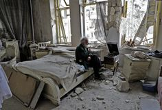 Mohammed Mohiedin Anis, or Abu Omar, 70, smokes his pipe as he sits in his destroyed bedroom listening to music on his gramophone in Aleppo's formerly rebel-held al-Shaar neighborhood on March 9. Photo by Joseph Eid/AFP/Getty Images