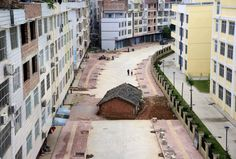 A nail house stands in the middle of a road in Nanning, Guangxi province, China in Land seizures by local officials over years of booming property development have been a problem in China. Nanning, In China, Chinese Buildings, Make Way, Meanwhile In, House Sitting, Property Development, Photos Of The Week, Under Construction