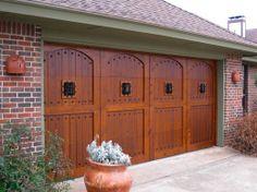 Wood garage door with iron speak easy grills and decorative clavos