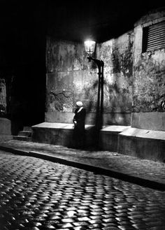 People of Paris: Woman standing under a Montmarte streetlight.  Photography by Alfred Eisenstaedt