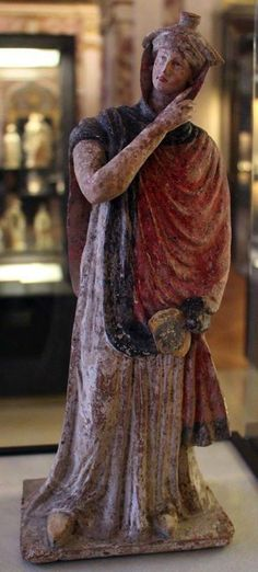 """The Greek woman. An elegant woman caught in the act of adjust the headgear, the """"tegidion"""", worn in weddings and still in the religious rites. IV century B. From Tanagra, Boeotia. Paris, the Louvre Museum Archaic Greece, Ancient Greece, Ancient Egypt, Ancient History, Art History, Classical Greece, Classical Period, Minoan, Mycenaean"""
