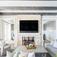Under a white plank ceiling accented with rustic wood beams, a flat panel television is fixed above a white mantel mounted to a double sided stone fireplace. Home Fireplace, Living Room With Fireplace, Fireplace Design, Fireplaces, Fireplace Ideas, Fireplace Surrounds, Living Room Goals, Home Living Room, Living Room Designs