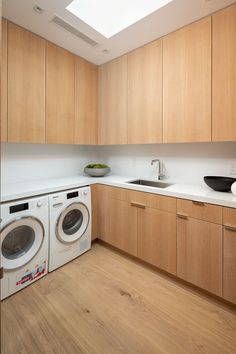 Laundry Room Ideas - This modern laundry room features floor-to-ceiling wood cabinets, a skylight, and plenty of counter space. Modern Laundry Rooms, Kitchen Modern, Hidden Lighting, Integrated Fridge, Limestone Wall, Small Outdoor Spaces, White Oak Floors, Island With Seating, Wood Vanity