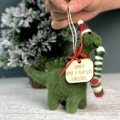 This personalised dinosaur Christmas Decoration made from felt is the perfect Christmas Tree decoration this yearCan be personalised by adding a wooden tag around the dinosaur's neck.This gorgeous, on trend felt dinosaur with a personalised wooden tag and a stripey Christmas stocking in his mouth is the perfect Christmas Tree decoration with a difference this year! The personalised dinosaur bauble will soon become the favourite decoration to put on the tree every year and is the perfect gift… Christmas Messages, Felt Christmas, Winter Christmas, Christmas Stockings, Christmas Crafts, Christmas Ornaments, Dinosaur Christmas Decorations, Personalised Christmas Decorations, Homemade Ornaments