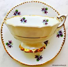 Beautiful Royal Stafford Sweet Violets purple and white footed tea cup and saucer featuring elegant gold frill details. Set is in good antique condition with no chips, cracks or crazing. There is a small fleck of paint loss on the cups foot as shown in the photos, price reduced