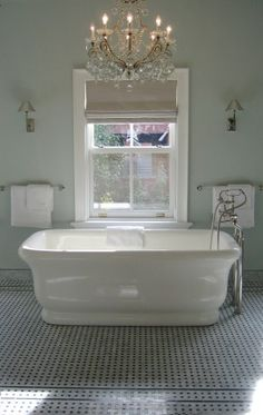 Deze romantische badkamer met losstaande kuip is prachtig voor in een klassieke woning. De mooie kroonluchter maakt het plaatje af.