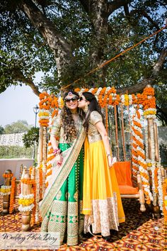 Sister of the Bride - Green and Yellow Anarkalis | WedMeGood | Bride in a Golden and Green Floor Length Anarkali and the Sister in a Yellow and Silver Anarkali with Genda Phool Decor #wedmegood #anarkali #indianbride #indianwedding
