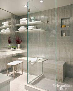 """Designer Frank Roop  installed molded-aluminum Ann Sacks  tile """"subway style,"""" but vertically. A mitered marble bench appears to run through the glass shower enclosure.   - ELLEDecor.com"""