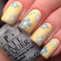 A really cute and light spring nail art design. Play along with baby blue and yellow colors as you paint on polka dots and flowers unto each nail. #springnaildesigns