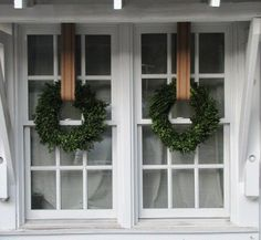 Boxwood wreaths hung from burlap ribbon, like these via Tracery Interiors, are simple and elegant:
