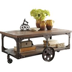 Add industrial flair to your living room or library with this wheeled coffee table, featuring a cart-inspired design and planked wood top.  ...