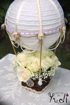 This beautifully handcrafted Hot Air Balloon centerpiece is made using a white paper lantern that has been adorned with high quality ivory and gold ribbon, burlap ribbon, white lace. Decorated with pearl and ivory ribbon draping and embellished with burlap and satin ivory bows. The lantern is attached to a natural brown basket using wooden dowels that are hand painted to match. Each centerpiece will come with a tag with either TABLE NO. or Mr and Mrs. Customization available. ** TWO STYLE...