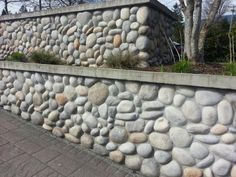 A length of stone wall along the border of a garden or yard is an enduring reminder of the past, yet it is compatible in urban areas with contemporary designs and lifestyle. Rock Wall Landscape, Rock Retaining Wall, Garden Wall Designs, Stone Wallpaper, Rain Garden, Cabins And Cottages, Garden Seating, Private Garden, Backyard