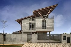 Completed in 2015 in Sepang, Malaysia. Images by Marc Tey. The Sepang House is defined by a large sheltering roof with deep overhangs, shaded terraces and balconies along its edges. It uses raw concrete,. Concrete Facade, Exposed Concrete, Concrete Bricks, Sepang, Roof Design, House Design, Brick Architecture, Roof Structure, Unique Buildings