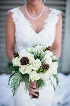 White rose bridal bouquet winter design with pime cones and green winter greenery