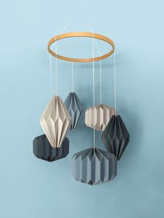 """A stunning hand crafted hanging mobile consisting of six individual geometric shapes folded from specialty stocks. A beautiful wooden """"halo"""" hovers above—complementing the materials below. A unique display worthy of any nursery or child's room. Nursery Room, Nursery Decor, Hanging Mobile, Kidsroom, Geometric Shapes, Baby Shop, Wind Chimes, Babyshower, Halo"""