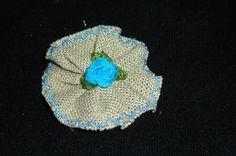 Flor de lino con festón azul cielo, rosita central conjuntada con el festón