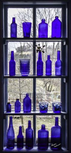 Cobalt blue glass bottles, etc., on shelves in window Blue Glass Bottles, Cobalt Glass, Old Bottles, Blue Bottle, Antique Bottles, Vintage Bottles, Vintage Perfume, Antique Glass, Perfume Bottles