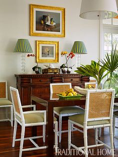 A brown Parsons-style table contrasts with caned bamboo chairs that don bright white-painted frames. - Photo: Robert Brantley / Design: Gary Mcbournie