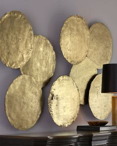 """Four Oil Drum Lid Art Pieces at Horchow.  Disks are handcrafted of resin and finished with hand-applied gold leaf.  Each disk, 21""""-22""""Dia. $475.00"""