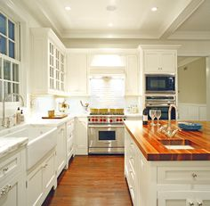 Wood floors, butcher block island, wolf range, white cabinets, marble countertops, farmhouse sink