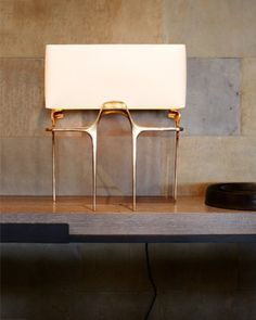 The Flint table lamp of polished bronze by CASTE
