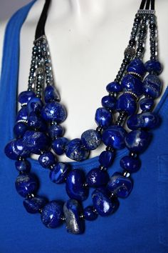 This triple strand cobalt blue stone necklace was hand sculpted from clay to emulate blue lapis lazuli stones. The handmade stones are combined