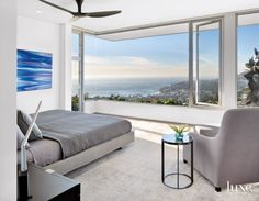 In the master bedroom, the Minotti bed looks out to a view of the Pacific. The chair and the black marble table are both by Maxalto and are from Diva Group; the cut-pile-silk rug is by Aga John Oriental Rugs. The painting by Andy Moses from William Turner Gallery adds color.