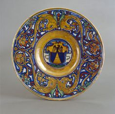"""Workshop of Maestro Giorgio Andreoli of Gubbio, 1465/1470- 1553. Italian maiolica, 1524, """"Plate with border of foliate scrollwork with dolphin heads and cornucopias, in the center, shield of arms of Vigerio of Savona."""