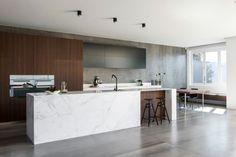 cuisine minimaliste contemporaine aménagée avec un îlot en marbre blanc, armoires en noir et blanc et noyer, mur recouvert de carrelage béton ciré et coin repas