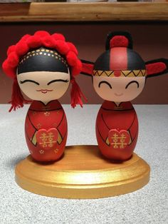 Custom handmade wedding kokeshi cake topper by ohmissco on Etsy. Couple in traditional Chinese qun kwa and holding hearts with the Chinese double happiness symbol. {www.ohmissco.etsy.com}