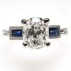 $10,499 1.5 ct Cushion cut diamond & blue sapphire engagement ring in 14K white gold; Almost all the cost is in that huge diamond.  Swap it out and it should probably be in our price range.